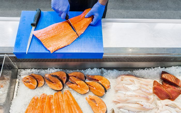 how to buy salmon Cropped Image Of Fish Vendor Cutting Salmon At Refrigerated Section In Supermarket