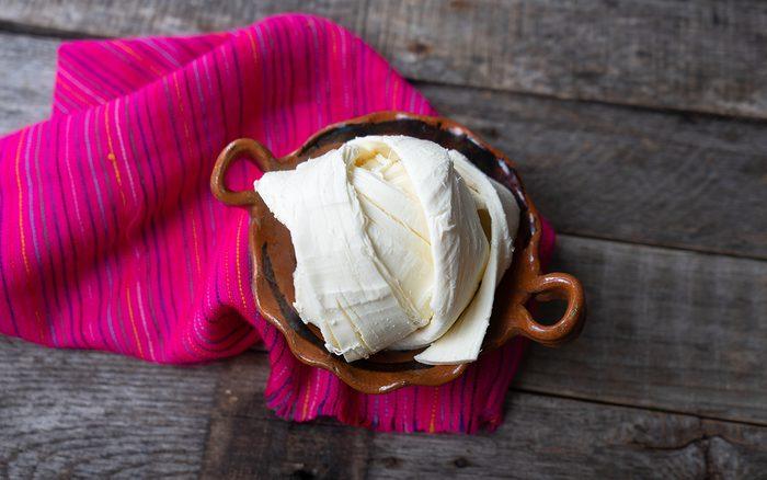 Fresh Oaxaca Cheese In Clay Pot On Wood Background