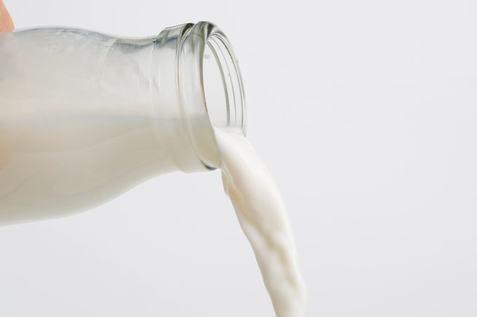 Pouring heavy cream From A Glass Bottle.