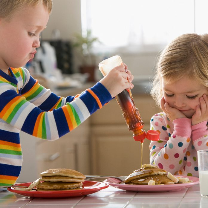 Caucasian Boy Pouring Syrup On Sister's Pancakes
