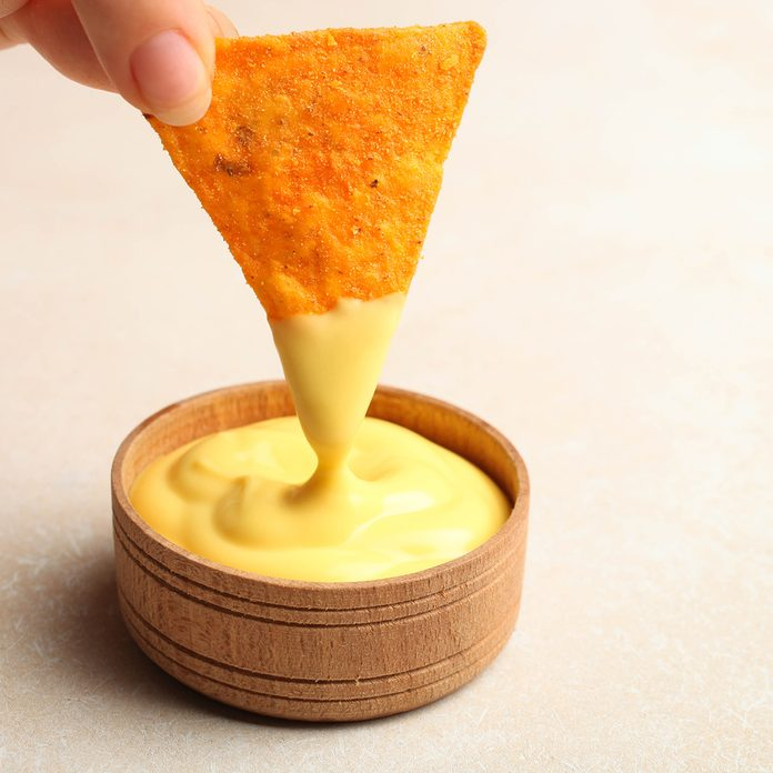 Mexican crispy snack, nachos chips and cheese sauce on neutral background.