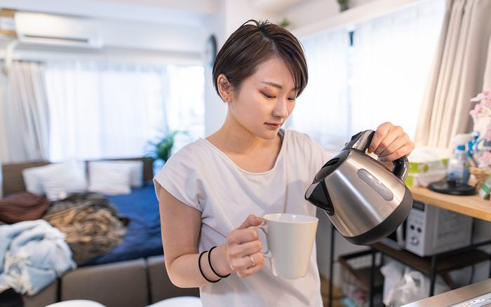 electric tea kettle review Young Woman Pouring Coffee For Breakfast