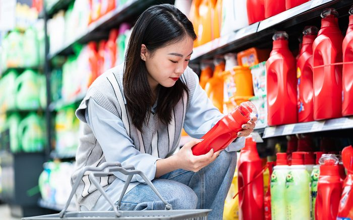 Asian Woman Looking for Best Laundry Detergent In Supermarket