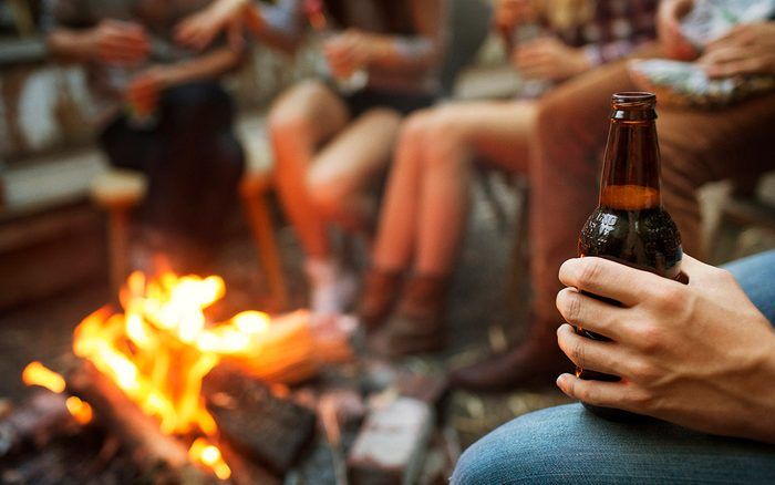 Cropped Image Of Man Holding a Beer Bottle While Camping With Friends