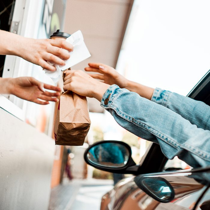 Young woman sitting in her car eating fast food and drinking soda and coffee. In a rush, multi tasking, eating take out burger, french fries and dessert while driving a car. Paying with credit card at drive through. Receiving a receipt and ordered food.