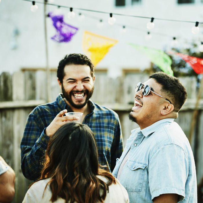 Laughing friends hanging out during backyard barbecue on summer evening