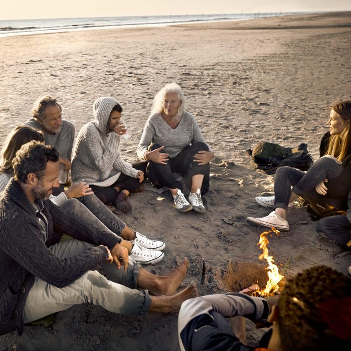 Family and friends sitting around campfire on the beach at sunset