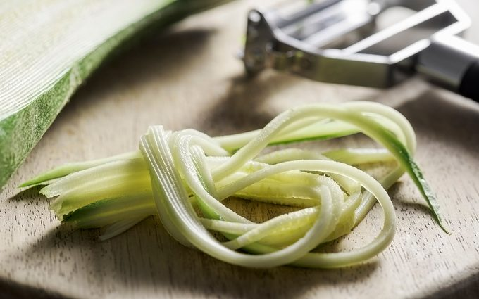 how to grate zucchini Strands of a julienned courgette are lying at the front of a wooden chopping board. The Julienne utensil and the rest of the courgette are lying behind it. The peeler is made from stainless steel and has a black handle. The selective focus is on the courgette in the foreground.