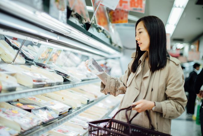Young Asian woman grocery shopping and choosing fresh poultry in supermarket