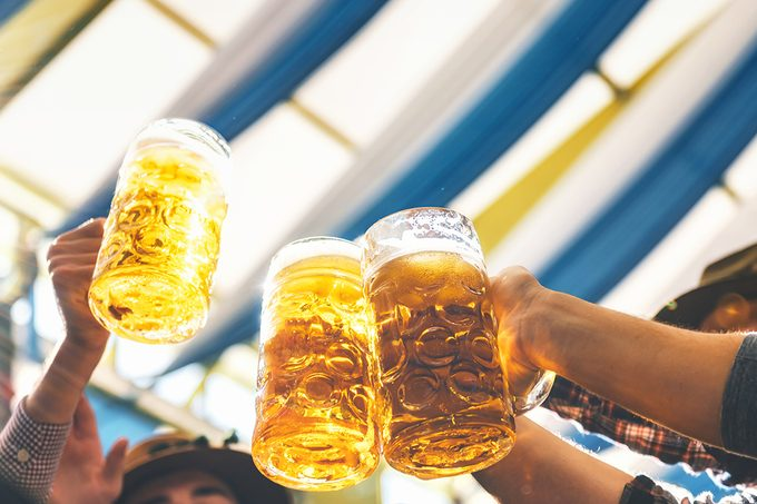 People Clinking Mass Beer Glasses At Oktoberfest In Munich