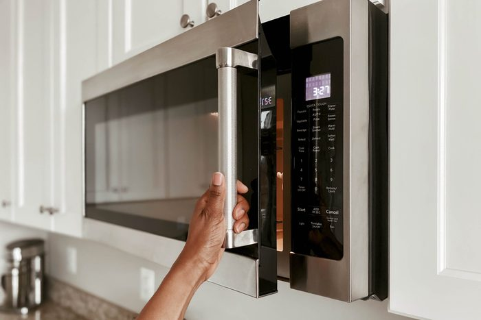 Close-Up of Woman Opening Microwave