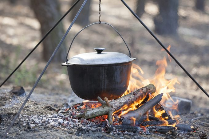 dutch oven over a campfire in the woods