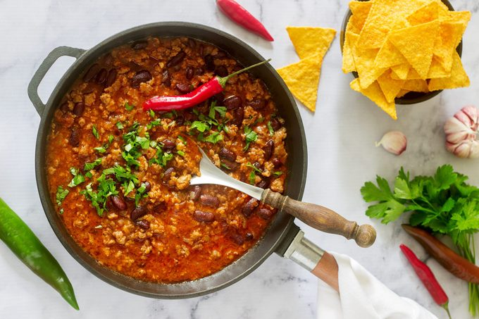 Mexican and American food Chili con carne served with nachos, pepper and herbs.