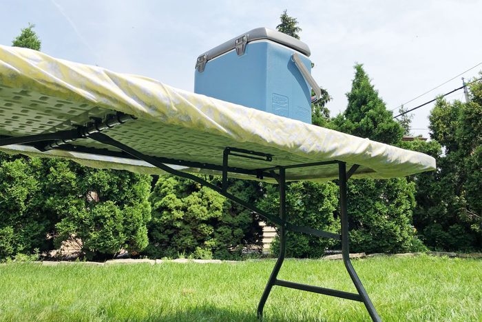 twin fitted sheet tablecloth around an outdoor folding table