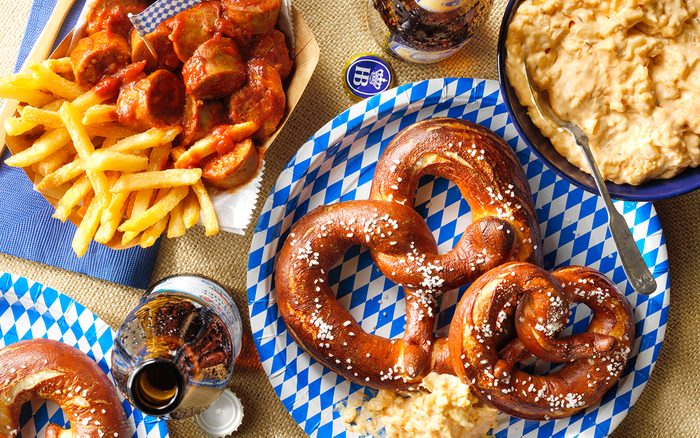 Chewy Soft Pretzels; Obatzda German Cheese Dip; Currywurst; overhead camera angle; pretzels; currywurst; fries; beer; beer bottle; wood surface; burlap; paper napkin; blue napkin; fork; wood fork; bamboo fork; cheese dip; opener; copy space; cheese dip; camembert chesse; cream cheese; onion; paprika; caraway seeds; salt; pepper; bratwurst; olive oil; inion; ketchup; chicken broth; brown sugar; red wine vinegar; curry powder; smoked paprika; dry yeast; flour; baking soda; egg; kosher salt; sesame seeds; poppy seeds; parmesan cheese; beer; pitcher; charcuterie board; octoberfest; german