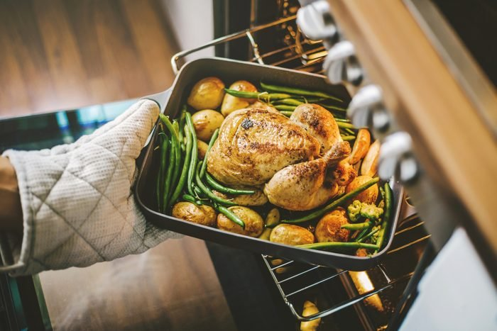 hand with an oven mitt removing a tray of chicken and vegetables from an open oven