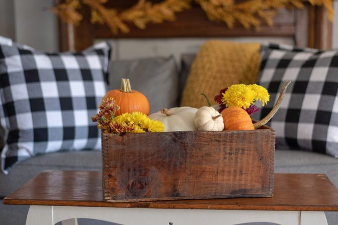 Vintage wooden crate filled with pumpkins and autumn flowers on a coffee table; couch with gingham pillows and a yellow throw blanket in the background