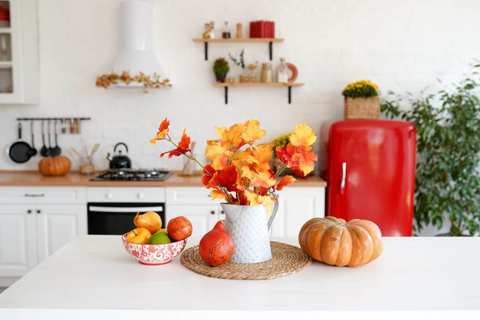 autumn table with vegetables and autumn decor in kitchen. red and yellow leaves in the vase and pumpkin on white background.
