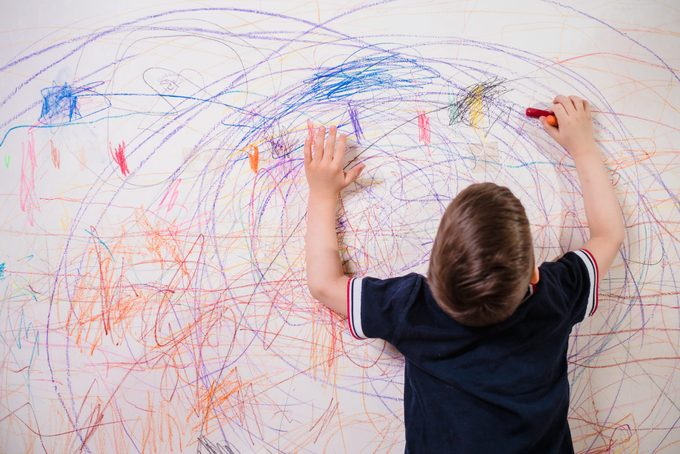 The Child Draws On The Wall With A Crayon. The Boy Is Engaged In Creativity At Home
