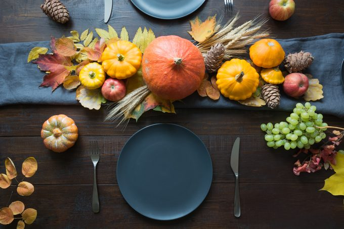 Autumn themed thanksgiving place setting with leaves, garland and pumpkins as decorations