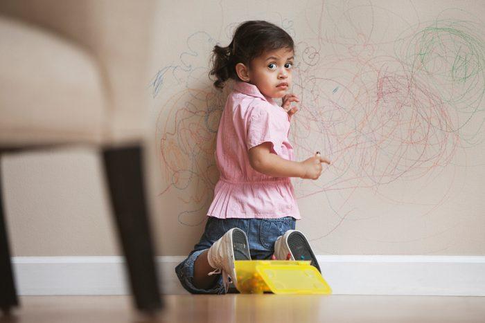 Hispanic girl drawing on wall