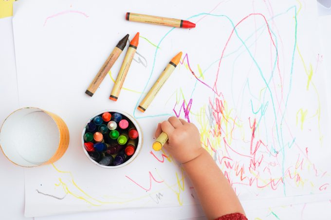 Baby's Hand Drawing On The White Paper With Colorful Crayons