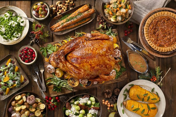 overhead view of thanksgiving dishes around a roasted turkey arranged on a wood table
