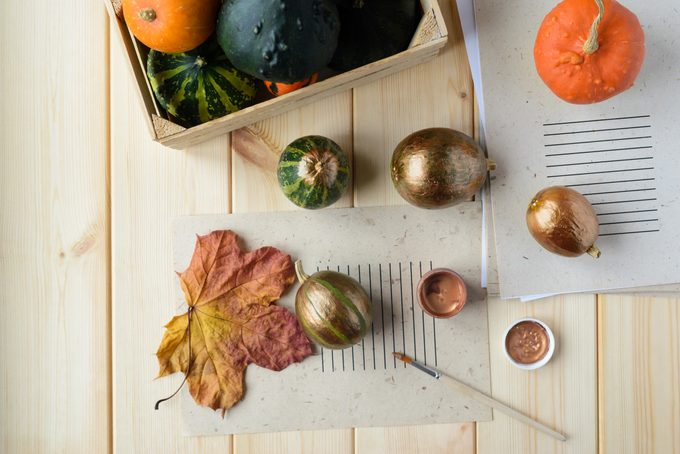 overhead view of supplies for diy autumn decor; painting pumpkins and gourds bronze on wood table background