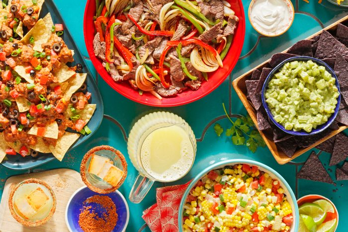 overhead view of colorful tex-mex food, nachos, fajitas, chips and guacamole, corn salsa, and a pitcher of margaritas on a teal tiled table