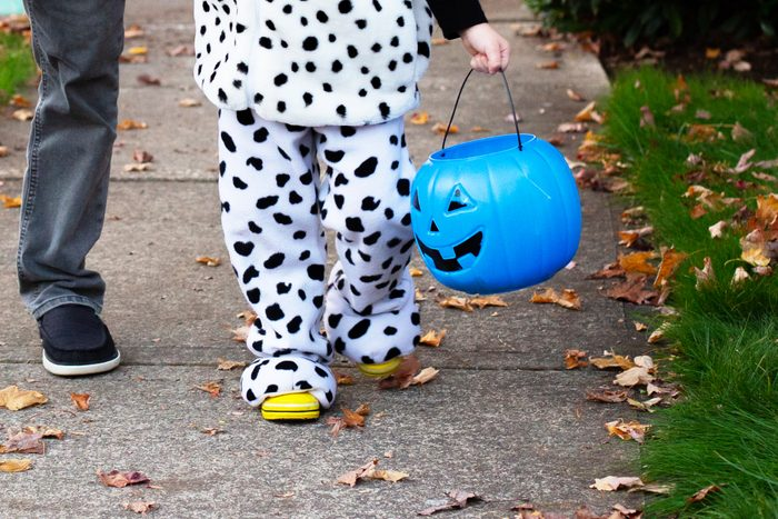 child Trick Or Treating with a blue halloween bucket