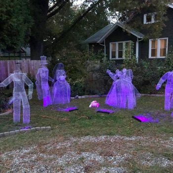 Chicken Wire Ghost Group Outdoor Halloween Decor in the yard of a house at twilight