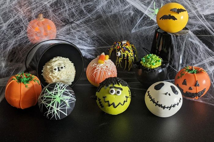 Halloween Hot Cocoa Bombs arranged on a black surface with spider web background